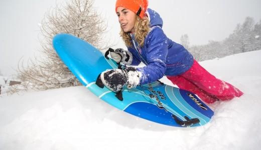 Tjej åker Snow Rocket i snö