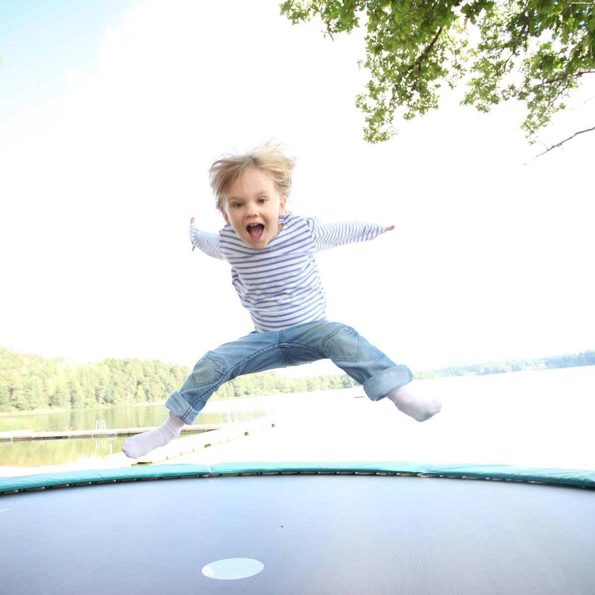 Liten flicka hoppar på studsmatta