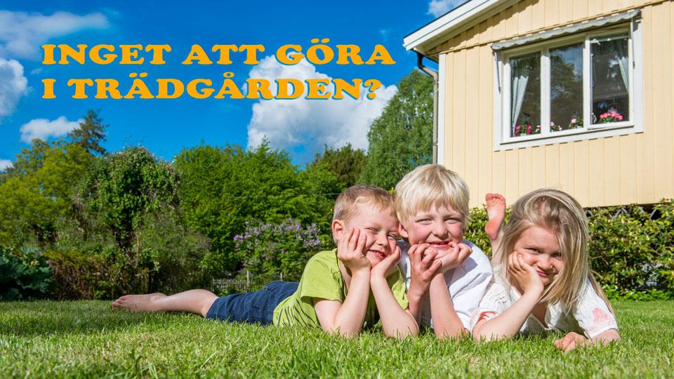Tre barn ligger på gräsmatta