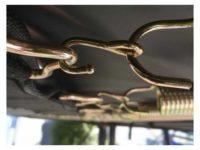 Krokar monterade mellan fjäder och duk på studsmatta